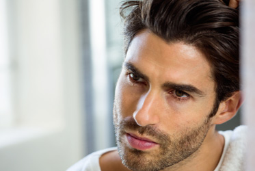 Man with dark hair promoting lipostructure fat transfer into face or scalp treatment
