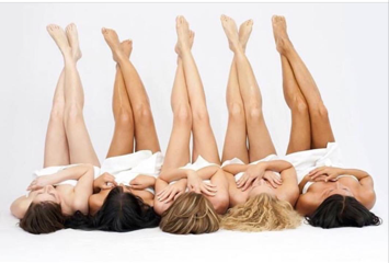 Four women laying down with legs crossed in the air