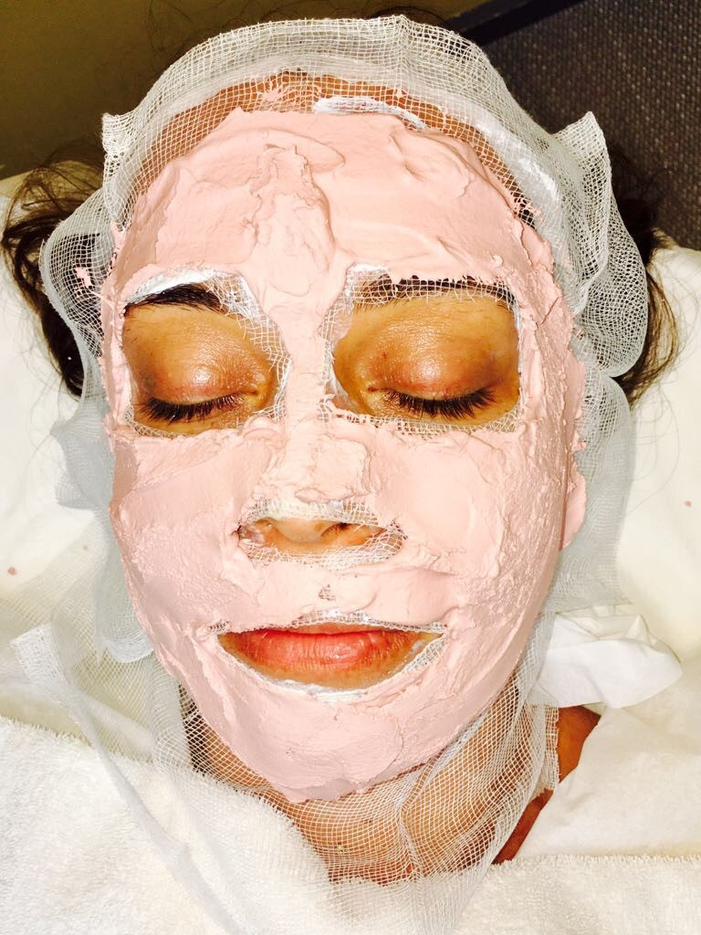 Woman receiving thermo heating mask for deep cleansing facial