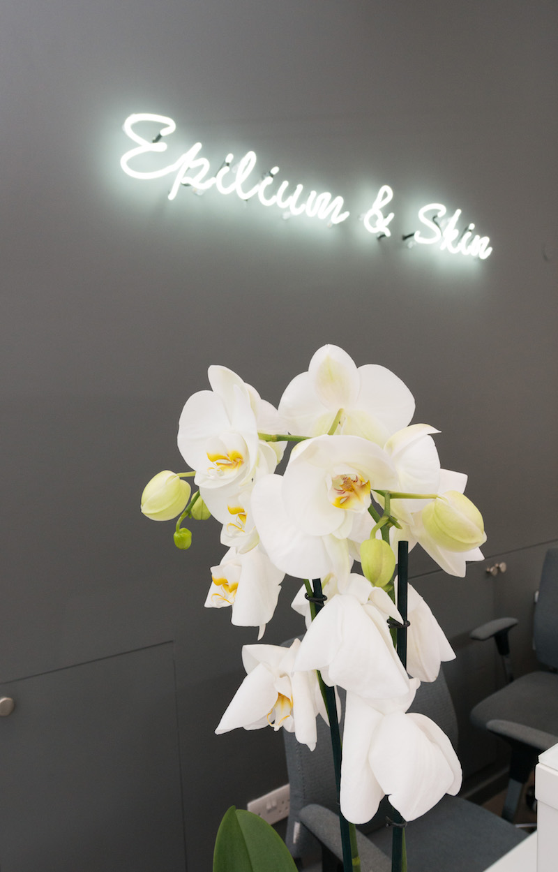 Wall in neon sign that says 'Epilium & Skin' with vase of flowers
