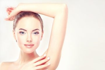 Woman with arm raised above head promoting laser hair removal treatment for women