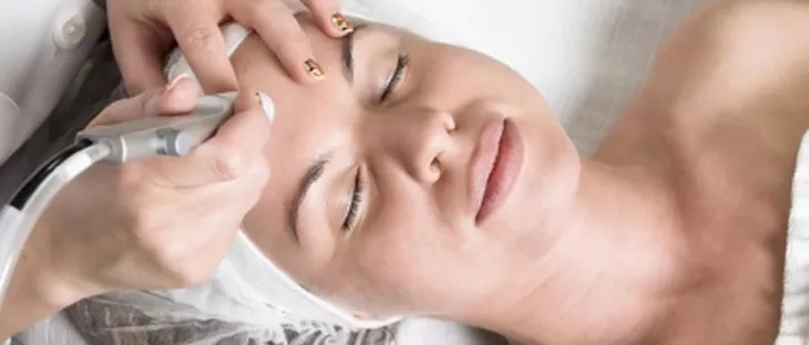 Woman receiving medican microdermabrasion treatment on forehead