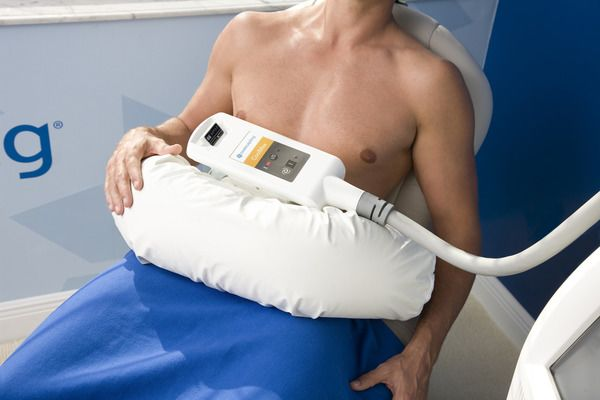 Man receiving coolsculpting treatment with machine around waist